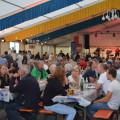 Foto des Inneren des Festzelts, Menschen auf Bierbänken sitzend und feiernd