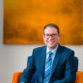 Bürgermeister Frank Zimmermann nach links schauend, sitzend auf Sofa, vor orangenem Bild, hochkant